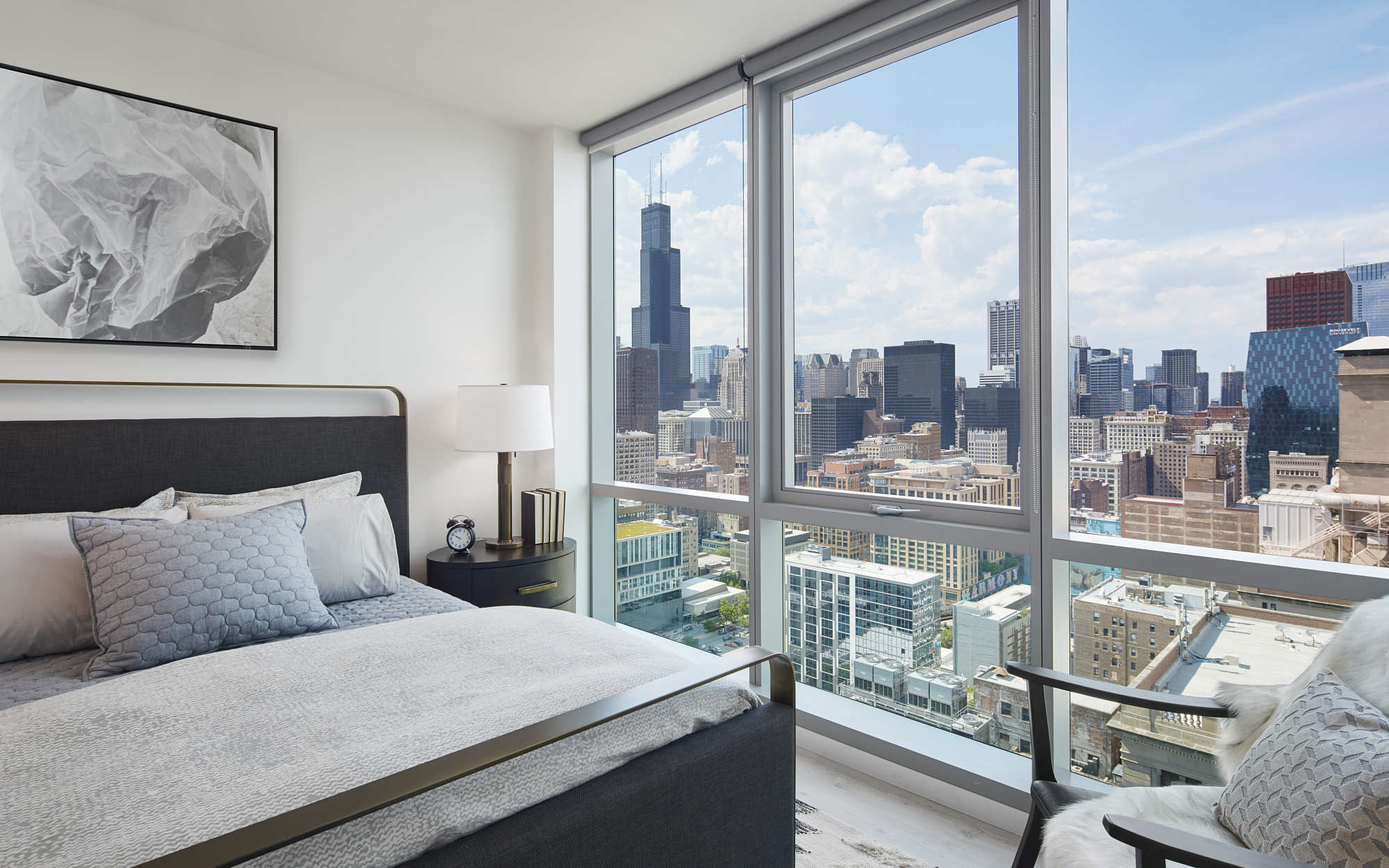 Essex Bedroom with open windows and skyscraper view
