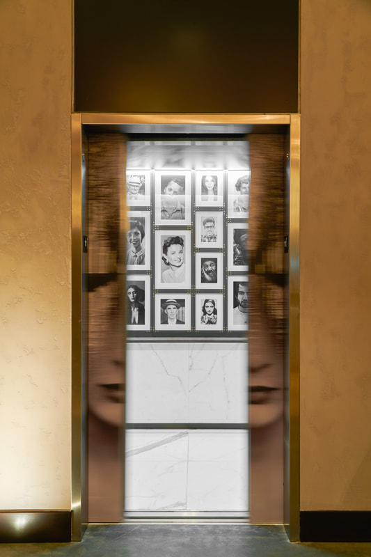 Mid closing elevator door with portrait wall in background