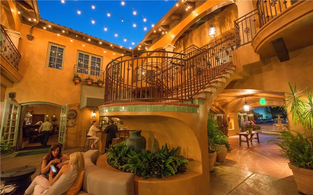Open-air lobby with terracotta walls, winding staircase, and seating for guests