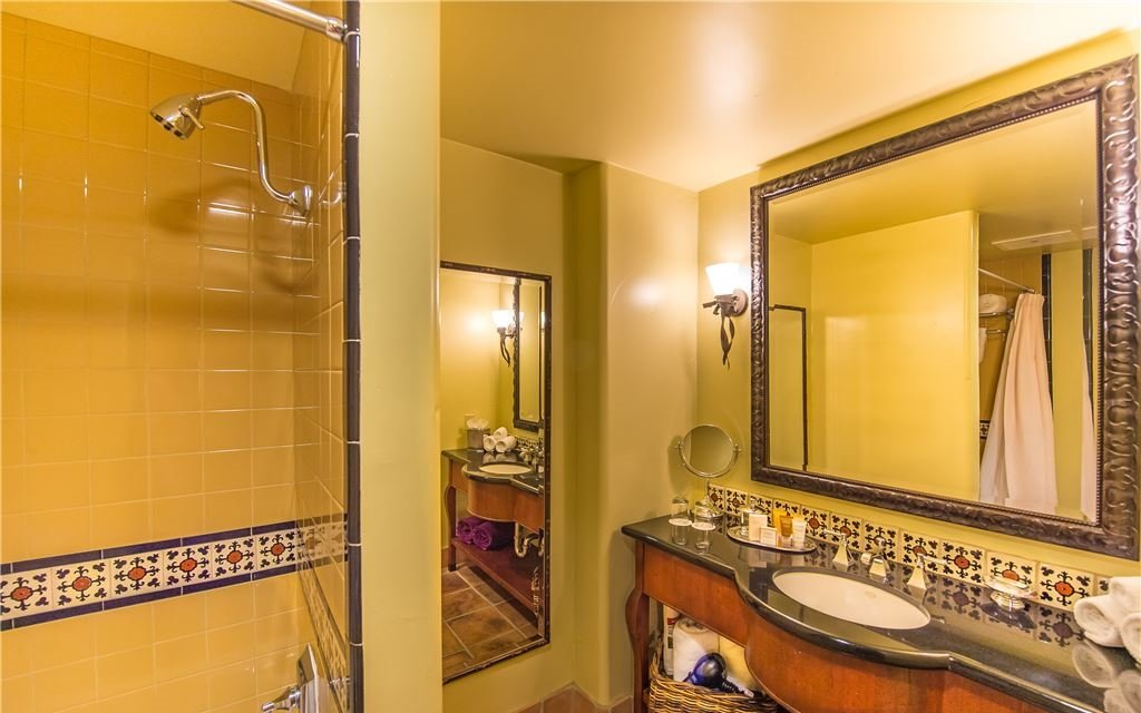 Yellow tiled shower and single-sink countertop