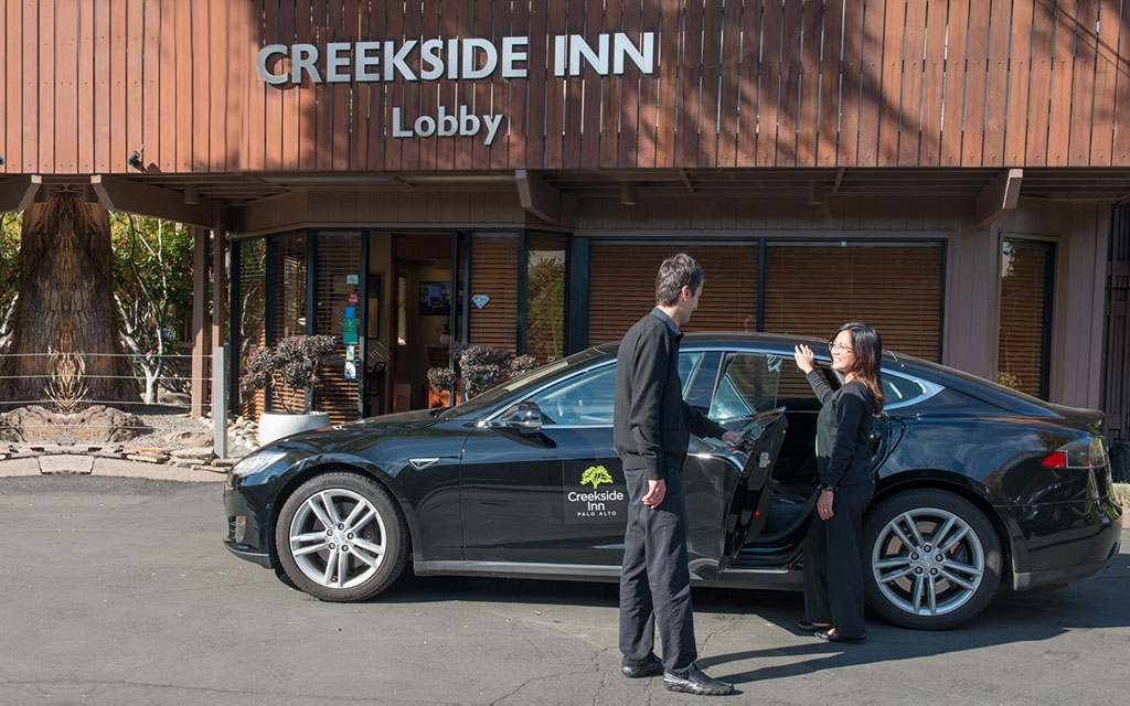 Man holds a car door open for a woman outside the Creekside Inn