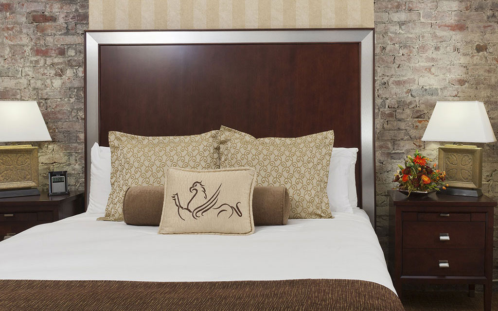 Large plush bed topped with pillows bearing the Hotel Griffon logo