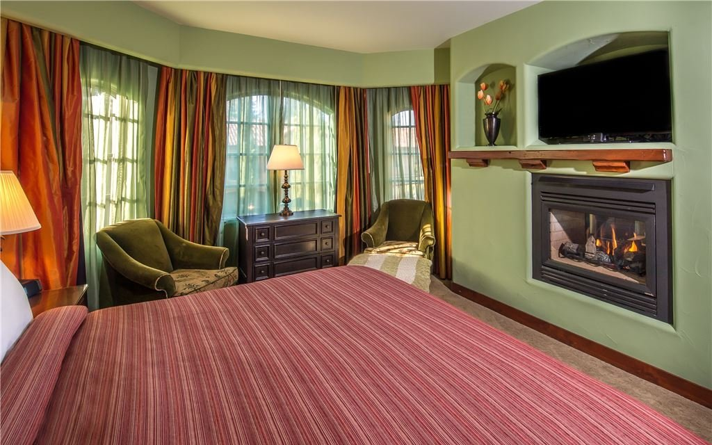 Large bed, fireplace, and TV in room with several large curtained windows
